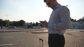 Young businessman standing on street near airport with suitcase and using smartphone. Handsome business man in. Sunglasses with smart phone near office. Sun stock video footage