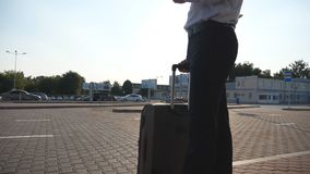Young businessman standing on street near airport with suitcase and using smartphone. Handsome business man in. Sunglasses with smart phone near office. Sun stock footage