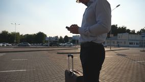 Young businessman standing on street near airport with suitcase and using smartphone. Handsome business man in. Sunglasses with smart phone near office. Sun stock video
