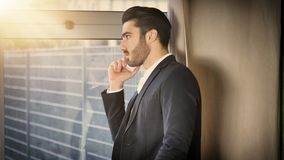 Young businessman standing and talking on photne. Handsome young businessman in his office talking on the phone, serious,leaning against a window Stock Photo