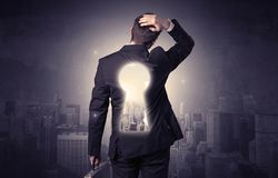 Businessman standing with keyhole on his back. Young businessman standing and thinking with keyhole on his back and city graphic around Stock Photography