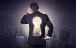 Businessman standing with keyhole on his back. Young businessman standing and thinking with keyhole on his back and city graphic around Stock Image