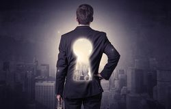 Businessman standing with keyhole on his back. Young businessman standing and thinking with keyhole on his back and city graphic around Royalty Free Stock Photos