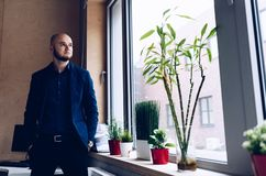 Young businessman standing by the window in the office stock photo