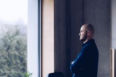 Young businessman standing by the window in the office royalty free stock photos