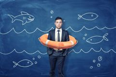 A young businessman stands inside an orange life buoy on a blue background with chalk waves and fish.