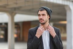Young businessman straightens shirt collar on blurred building background stock images
