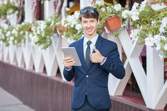 Young businessman in the street with tablet Stock Image