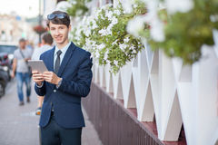 Young businessman in the street with tablet Stock Images