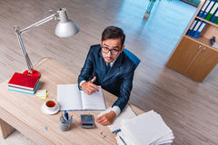 The young businessman in stress with lots of paperwork Stock Image