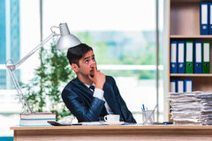 The young businessman in stress with lots of paperwork Royalty Free Stock Photos