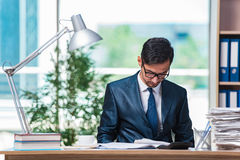 The young businessman in stress with lots of paperwork Stock Photo