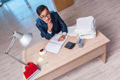 The young businessman in stress with lots of paperwork Stock Photography