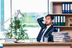 The young businessman in stress with lots of paperwork Stock Photos