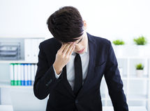 Young Businessman with stress rubbing his eyes Stock Photos