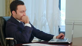 Young businessman stretching his arms in office and start working on laptop stock video