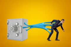 Young businessman stuck to bank safe with blue sticky slime on yellow background royalty free stock photos