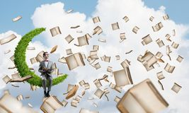 Young businessman or student studying the science and books flying around stock image