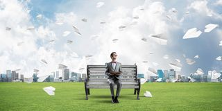 Young businessman or student studying the science and paper planes flying around Royalty Free Stock Image