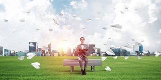 Young businessman or student studying the science and paper planes flying around Stock Images