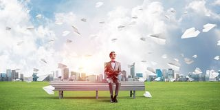 Young businessman or student studying the science and paper planes flying around Stock Image