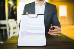Young businessman submitting resume to employer to review. Job application and interview concepts royalty free stock photography