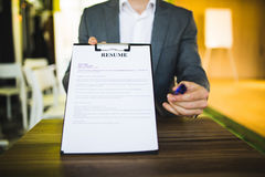 Young businessman submitting resume to employer to review Royalty Free Stock Photos