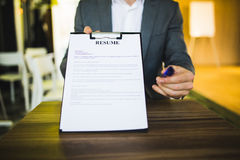 Young businessman submitting resume to employer to review Royalty Free Stock Photo