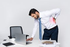 Young businessman suffering from backache while leaning at table. With laptop stock photography