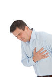 Young Businessman Suffering Chest Pain Problem. Close up Young Handsome Businessman Holding his Chest While Suffering From Angina Problem, Isolated on a White Royalty Free Stock Image