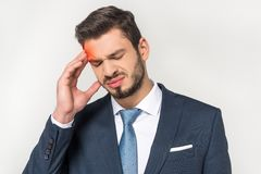 Young businessman suffering from headache. Isolated on grey Royalty Free Stock Images