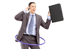 Young businessman in suit dancing with a hula hoop and talking o Stock Photos