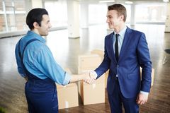 Relocation congrats. Young businessman in suit and delivery men in uniform handshaking after relocation work Stock Photo