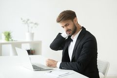Young businessman in suit feeling neck pain after sedentary work. Young businessman in suit feels neck pain massaging tensed muscles after sedentary work sitting stock photos