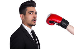 Businessman in suit gets hit, business agression. Young businessman in suit gets hit from person in boxing gloves, white background. Business agression royalty free stock photo