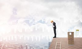 Engineer man standing on roof and looking down. Mixed media Royalty Free Stock Photo