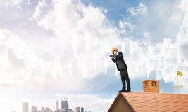 Engineer man standing on roof and looking in binoculars. Mixed media Royalty Free Stock Images