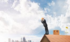 Engineer man standing on roof and looking in binoculars. Mixed media Royalty Free Stock Photography