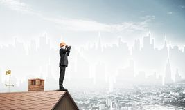 Engineer man standing on roof and looking in binoculars. Mixed m Stock Photos