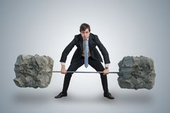 Young businessman in suit is lifting heavy weights. stock photography