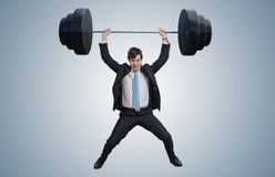 Young businessman in suit is lifting heavy weights. stock photos