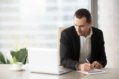 Young businessman in suit looking at laptop screen, taking notes Stock Images