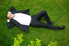 Young businessman in a suit lying on the grass, view from above Royalty Free Stock Images