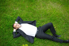 Young businessman in a suit lying on the grass, view from above Stock Photography