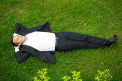 Young businessman in a suit lying on the grass, view from above Stock Photo