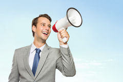 Young businessman in suit with a megaphone in his hand, smiling Stock Photos