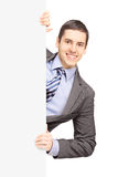 Young businessman in suit posing behind a blank panel Stock Photography
