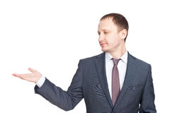 Young businessman in a suit presenting something Stock Images