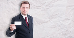Young businessman in suit showing blank visit card Stock Photos