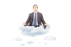 Young businessman in suit sitting on a cloud and meditating Royalty Free Stock Images
